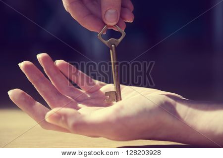 Female hand giving old key to other hand on blurred background