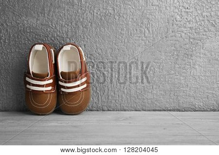 Brown baby shoes on grey textured background