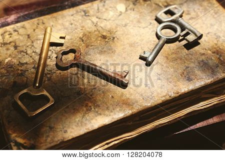 Four keys on background of old books