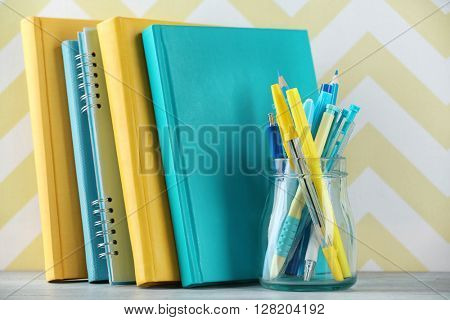 Stationery in glass jar on color background
