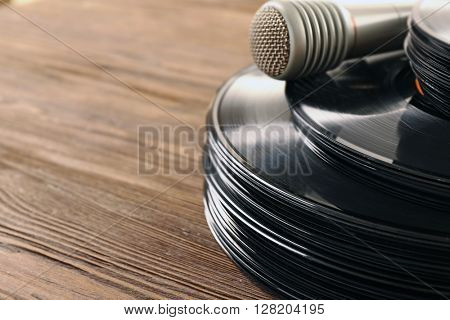 Stack of old vinyl records microphone on wooden background
