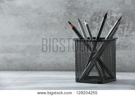 Pencils in metal holder in front of wall background