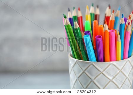 Pencils and markers in ceramic cup, closeup