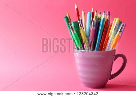 Colorful stationery in purple cup on pink background