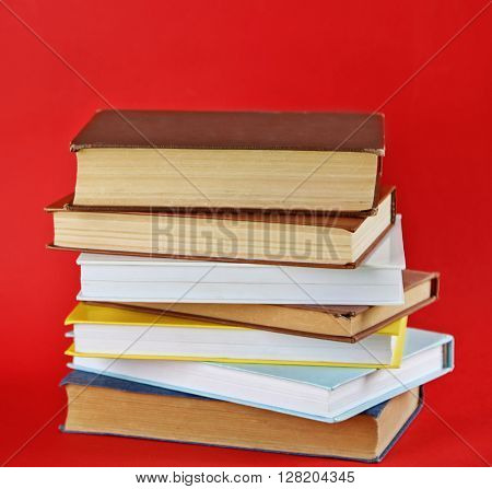 Stack of new and old books on red background