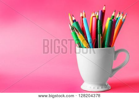 Colorful stationery in white cup on pink background