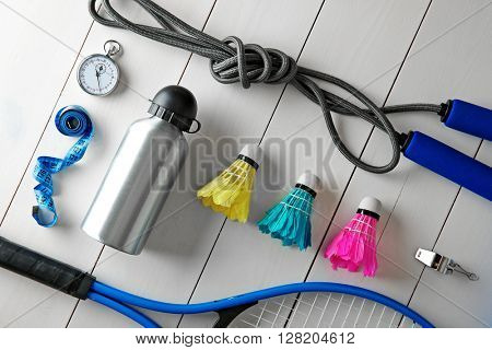 Sport equipment with bottle of water on white wooden background