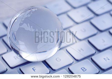 Crystal globe on laptop keyboard,  close up