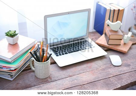 Workplace with laptop, table and books beside the window