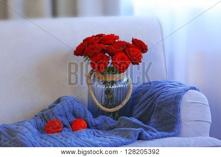 Glass jar of red roses on sofa