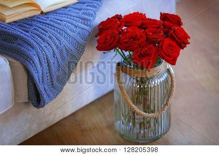 Glass jar of red roses on floor beside sofa