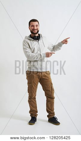 A young man in white hoody and khaki pants is smiling and pointing at something on his left