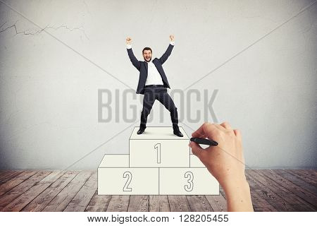 A businessman in dark grey suit is standing on the pedestal on the winner's place and is smiling happily with his fists raised