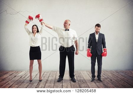 The referee is announcing the winner after a boxing match - it is the businesswoman and boxing gloves with her fists raised, while the businessman is the loser