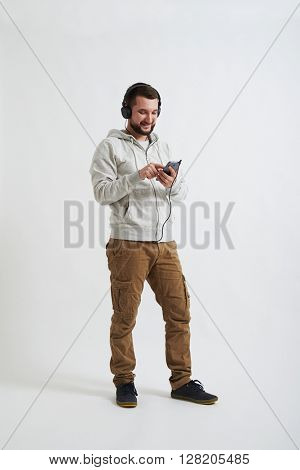 A young bearded man in casual clothes is watching and listening to something on the phone with his headphones on