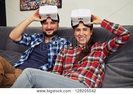 A young man and woman in casual clothes with virtual reality headset glasses on top of they heads resting on comfortable sofa
