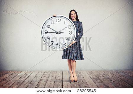A young smiling woman in checkered dress is holding a big round clock in her hands