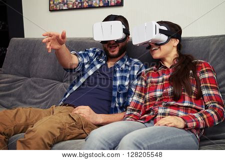A young man and woman in casual clothes and virtual reality glasses is discussing something