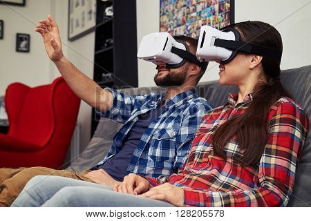 A young man and woman in casual clothes and virtual reality glasses is watching something and man trying to touch something in front of him