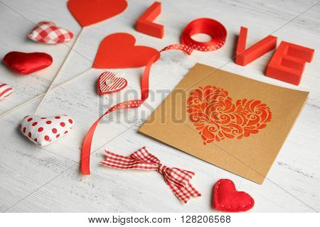 Valentine concept. Inscription love with hearts and card on wooden table background