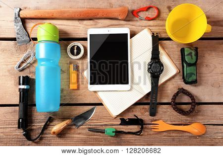 Tourism concept. Explorer equipment on wooden background, top view