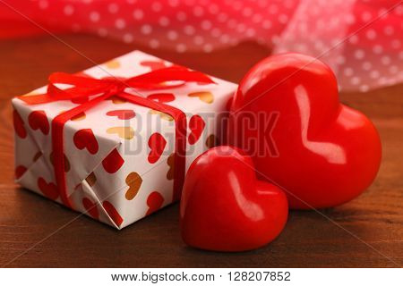 Gift box and decorative hearts on wooden table, on red fabric background
