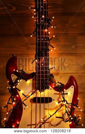 Electric guitar with lighted garland on dark wooden background