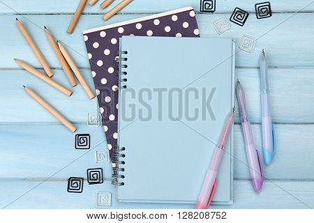 Office set with notebooks, colored pencils and pens on blue background