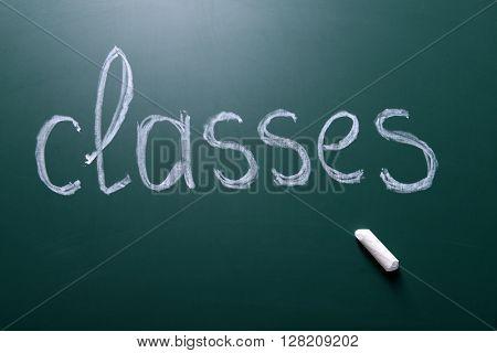 Classes inscription written with white chalk on blackboard