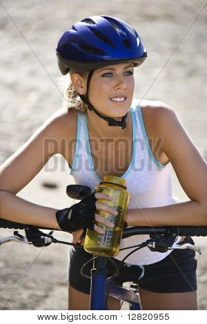 Caucasian mid-adult woman wearing bicycle helmet, sitting on bicycle, holding water bottle.