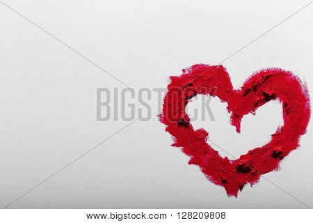 Red lipstick smeared in heart shape isolated on white background, close up