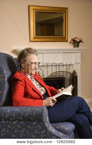 Elderly Caucasian woman reading book in chair at retirement community center.