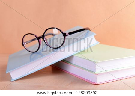 Pile of books and eyeglasses on it against beige background