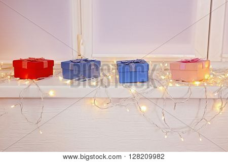 Colourful gift boxes and glowing lights are on window board, close up