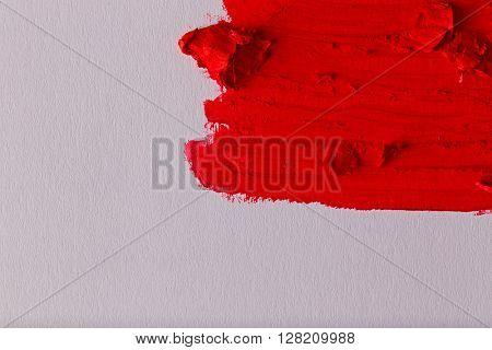 Smudged red lipstick on white background, close up