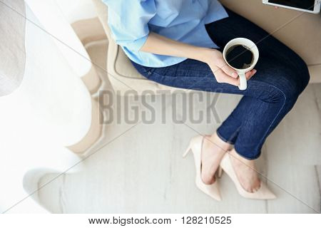 Woman holding a cup of coffee on her lap