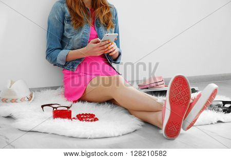 Young fashion blogger with her smart phone sitting on floor indoors