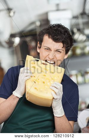Young Salesman Biting Cheese In Store