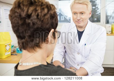 Doctor Looking At Female Patient Before Blood Donation