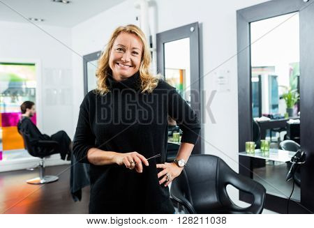 Hairstylist Holding Scissor While Standing In Salon
