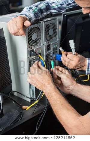 Senior Man And Technician Installing Computer In Classroom