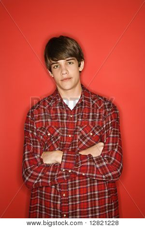 Portrait of Caucasian teen boy with arms crossed standing against red background wearing flannel shirt.
