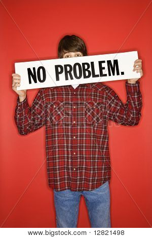 Portrait of Caucasian teen boy holding no problem sign under his eyes.