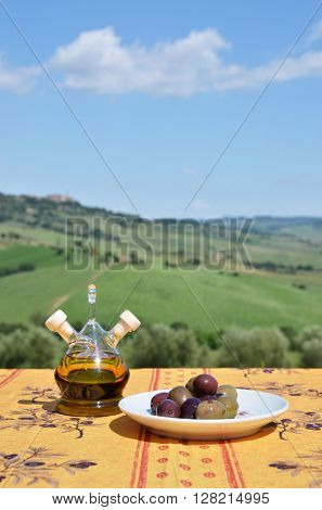 Oil and olives on the table against Tuscan landscape. Italy