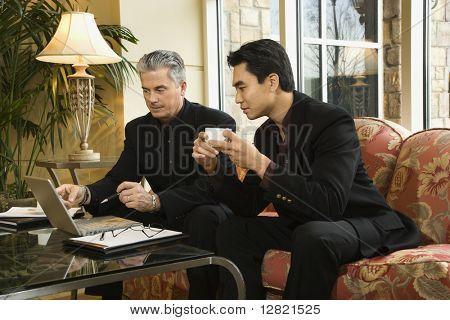 Prime adult Asian and Caucasian businessmen.