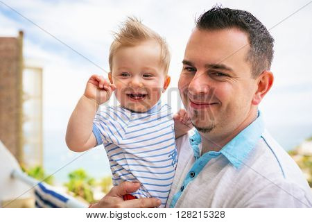 Happy baby boy with his father on holidays in Spain