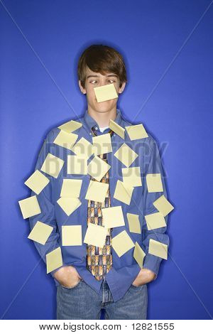 Portrait of Caucasian teen boy standing against blue background covered with blank sticky notes.