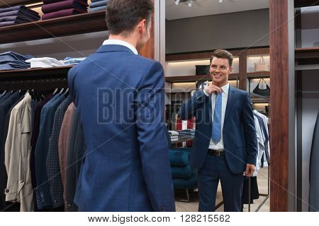Young man in suit at a mirror