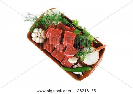 raw fresh beef meat slices in a ceramic dish with garlic and peppers isolated over white background