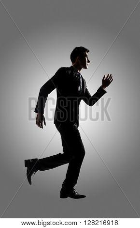Confident businessman running, silhouette portrait isolated